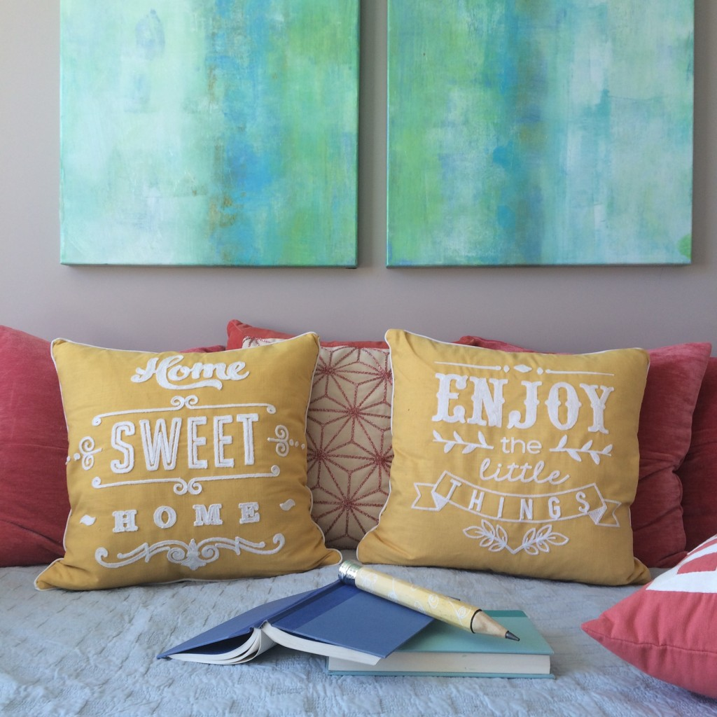 Home Sweet Home and Enjoy the Little Things pillows on a daybed with watercolor artwork on the walls