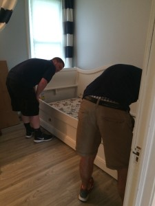 The Raymour and Flanigan delivery men balancing out the bed on the uneven floor!