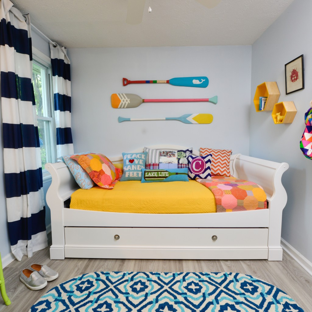 Mix and Match pillows and hand painted wooden paddle oars are the decorations in this small teen cottage bedroom with a white daybed and trundle