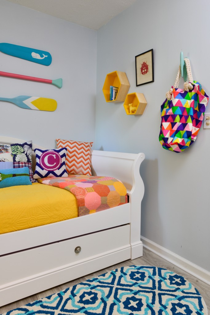 Mix and Match pillows and wall decor in this small girls room with a white daybed and hand potted oval rug in navy and turquoise