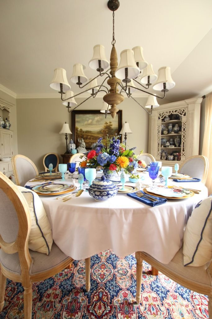 Tradtional_home_Easter_tablescape_setting_table_round_color_modern_mix_floral_arrangement_cobalt_delft_blue_dinnerware_dining_room_currey_company_chandelier_oriental_rug