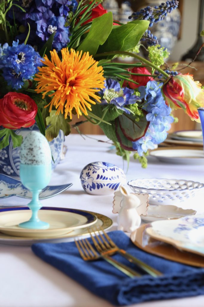 Tradtional_home_Easter_tablescape_setting_table_round_color_modern_mix_floral_arrangement_cobalt_delft_blue_dinnerware_dining_room_egg_amara_pip_studio
