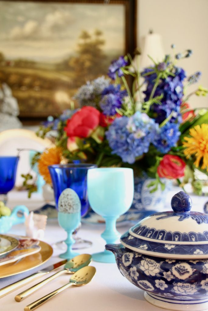 Tradtional_home_Easter_tablescape_setting_table_round_color_modern_mix_floral_arrangement_cobalt_delft_blue_dinnerware_dining_room_flowers_tulips_amara_pip_studio_gold_flatware