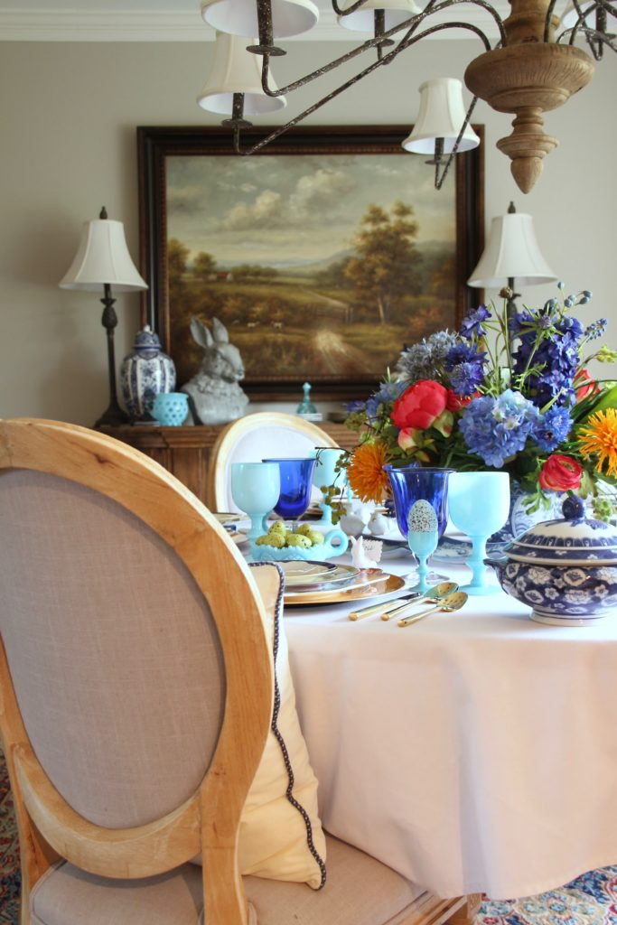 Tradtional_home_Easter_tablescape_setting_table_round_color_modern_mix_floral_arrangement_cobalt_delft_blue_dinnerware_dining_room_flowers_tulips_amara_pip_studio_landscape_painting