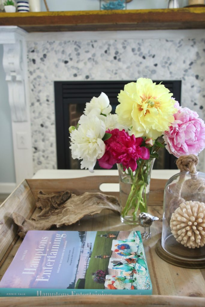 summer nautical decor on a wooden tray in front of a pebbled fireplace
