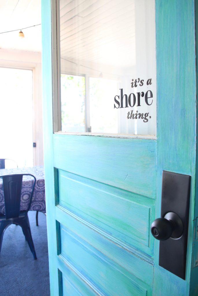 turquoise painted front door with decal on door