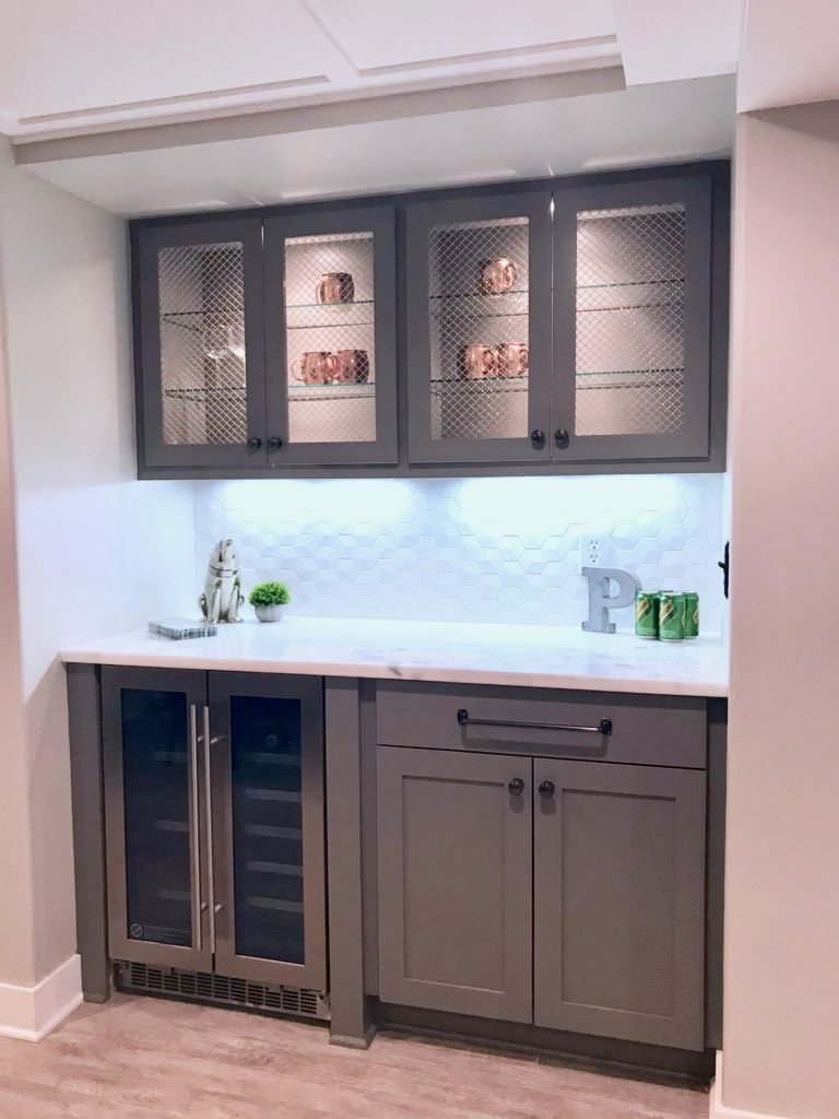 a closet gets turned into a small bar area with custom cabinets and white hexagon tile backsplash.