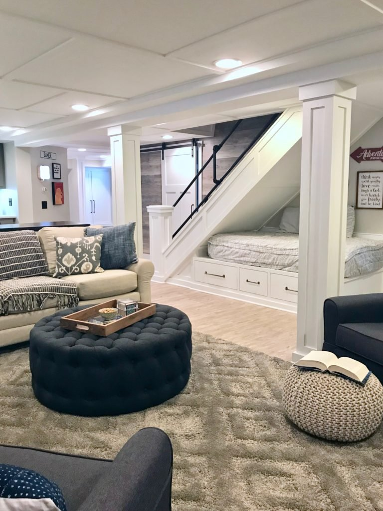 The full view of the farmhouse basement and the reading sleeping nook under the stairs. Neutral decor for this farmhouse style basement remodel