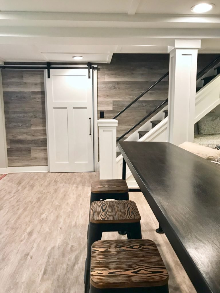 Farmhouse basement reclaimed wood wall accent and sliding barn door with black hardware. View of a bar height narrow dining pub table behind the sofa