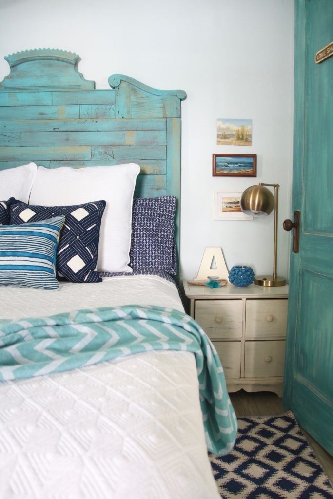 a hand painted turquoise blue headboard and door in this small cottage lakehouse