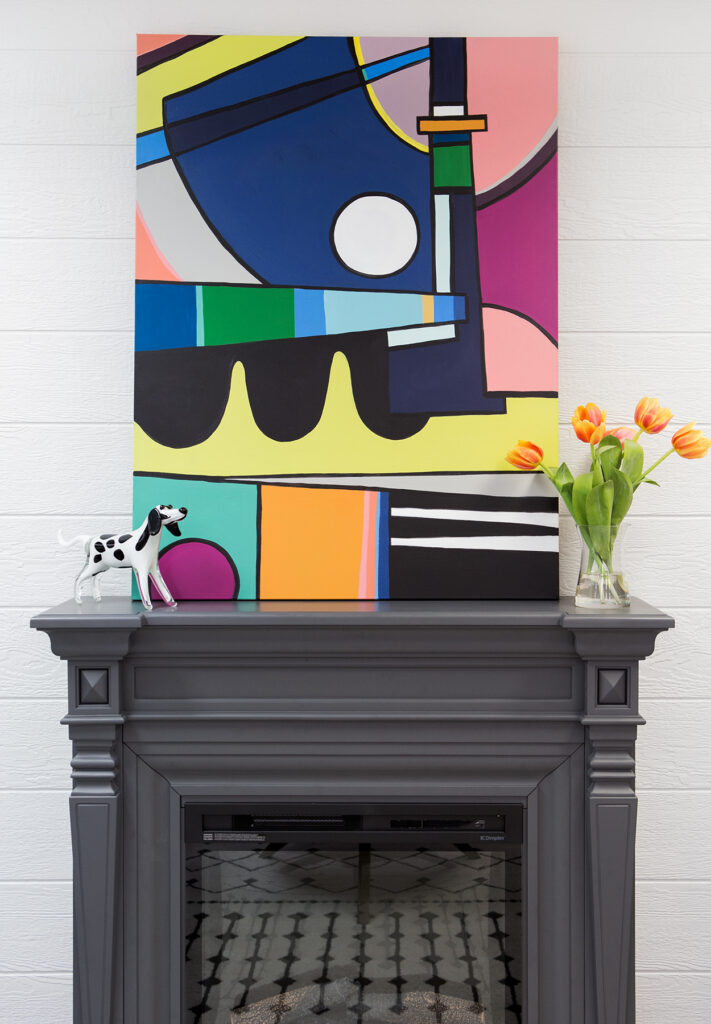 abstract canvas art painted by Amie Freling Brown hangs over a gray electric fireplace with a gray painted shiplap wall