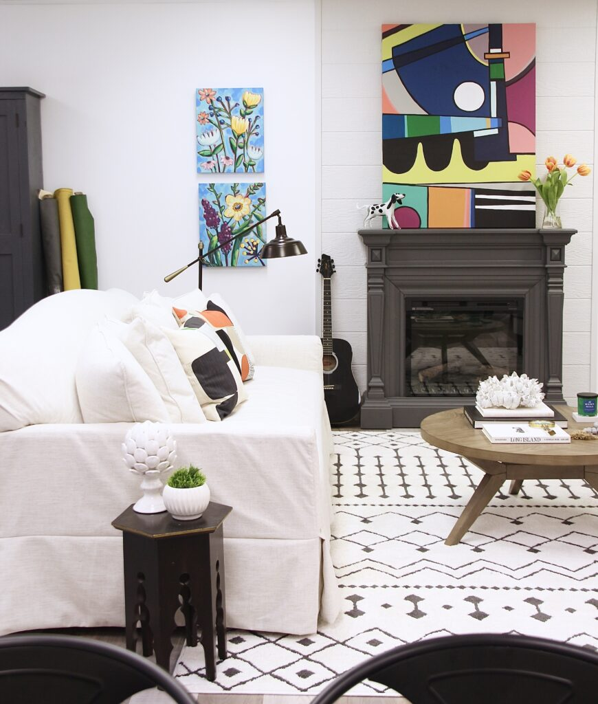 artwork from Amie Freling Brown of Meme Hill Studio hangs in a living room setting with Raymour & Flanigan furniture