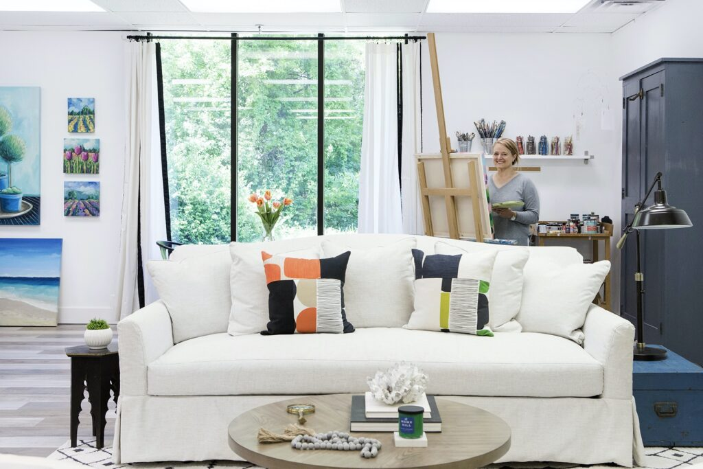 Amie Freling Brown paints in her new studio with a Raymour & Flanigan sofa in front with colorful accent pillows