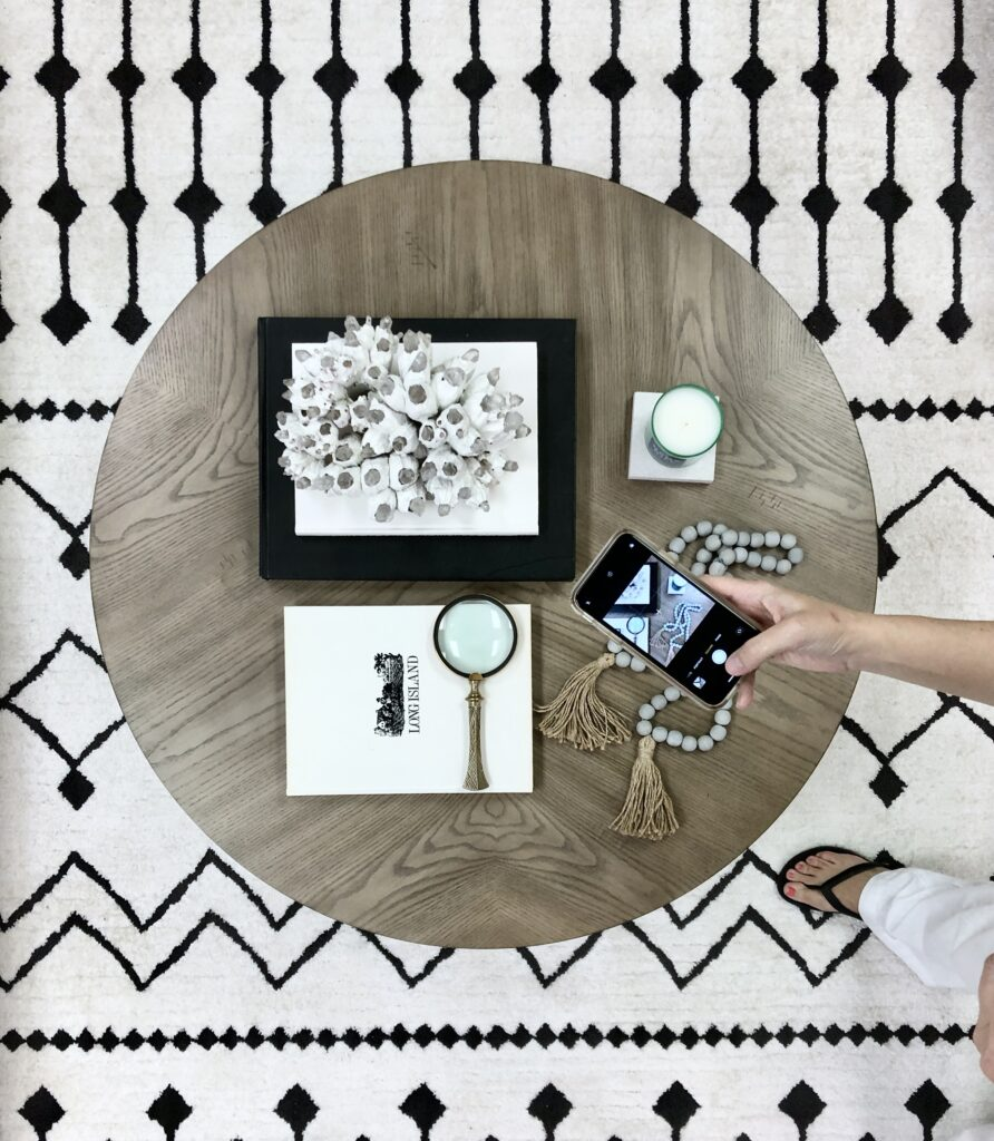 flat lay view of a round Nora coffee table from Raymour & Flanigan. The table is styled with black and white books and decorative accessories