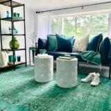 the turquoise vintage faded rug is the focal point in this small but cozy sitting area decorated with white garden stools and a navy blue sofa.