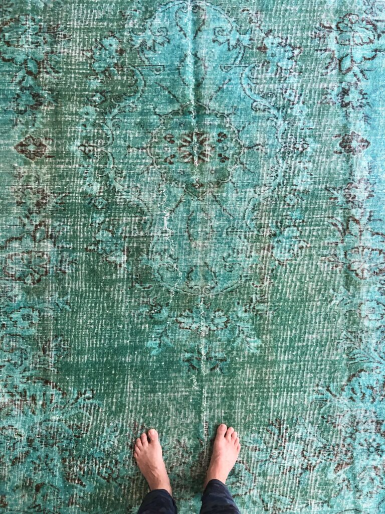the turkish one of a kind handover rug is laid out to see the design and natural wear of the vintage carpet