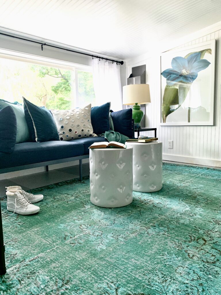 the sun shines through the white room with the green turquoise vintage Turkish rug on the floor in the center of the room.