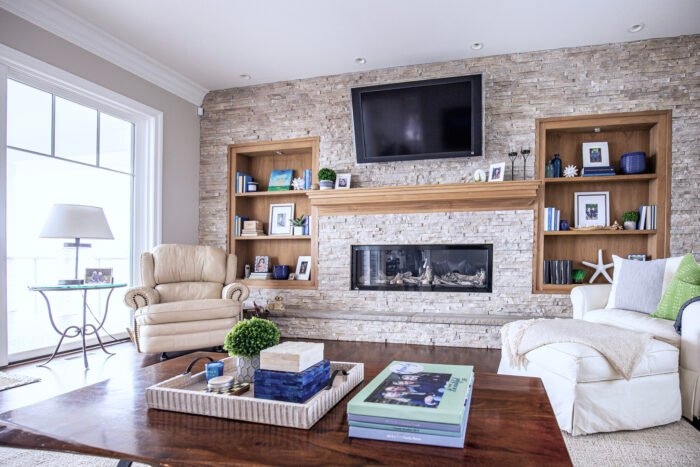 styling bookcases, stacked stone fireplace wall with wood shelves and built-in, and mantel