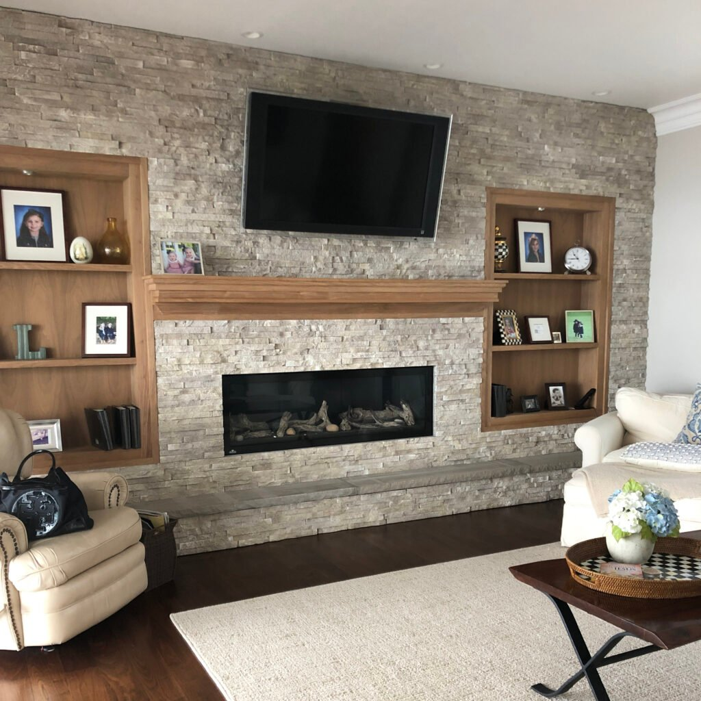 stacked stone fireplace, wood shelves< wood mantel, styling bookcases
