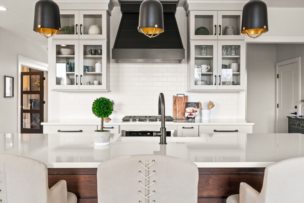 A modern farmhouse kitchen decorating ideas, an open floor plan kitchen with gray putty colored cabinets, a walnut wood ship lap island and white quartz countertops, detail of white matte subway tiles