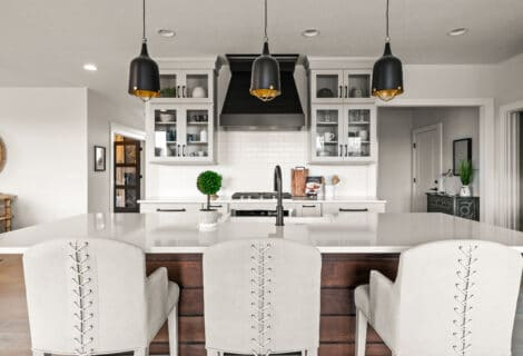 A modern farmhouse kitchen decorating ideas, an open floor plan kitchen with gray putty colored cabinets, a walnut wood ship lap island and white quartz countertops, simple clean lines of the cabinets