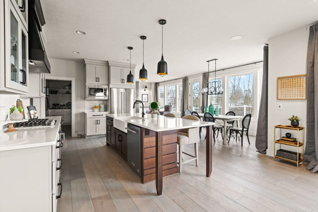 A modern farmhouse kitchen decorating ideas, an open floor plan kitchen with gray putty colored cabinets, a walnut wood ship lap island and white quartz countertops
