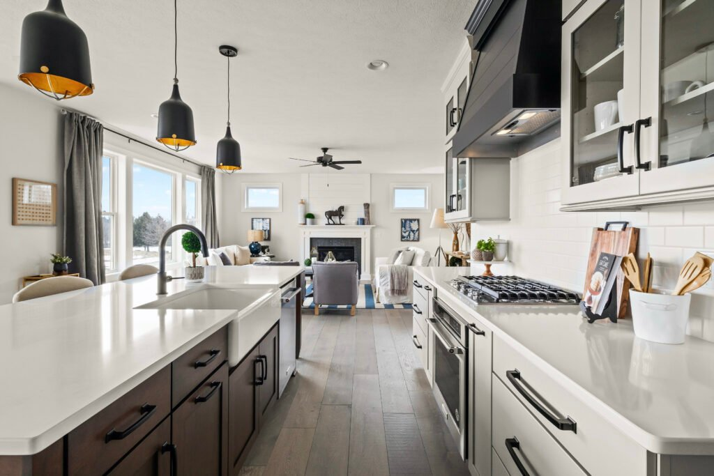 A modern farmhouse kitchen decorating ideas, an open floor plan kitchen with gray putty colored cabinets, a walnut wood ship lap island and white quartz countertops, wide plank white European plank flooring
